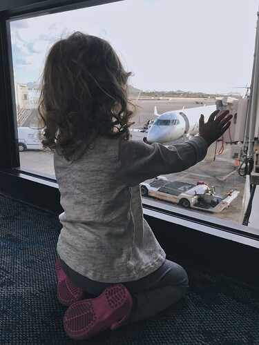 stock-photo-travel-window-airplane-hand-airport-watching-terminal-looking-out-little-girl-d7571dea-e439-4ecf-bf00-8875dd1bd658